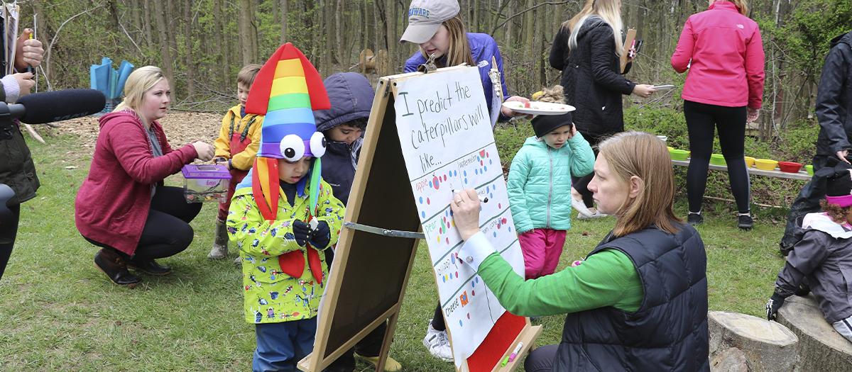 Professor Jen Gallo Fox and Lab School teacher help student do caterpillar activity outside