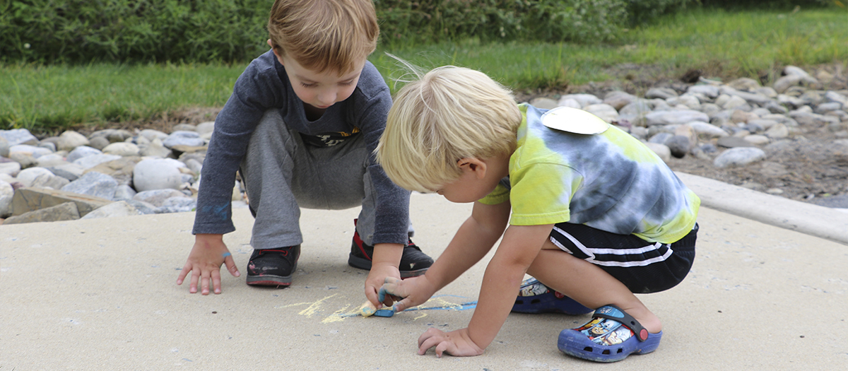 Two children draw with chalk on the sidewalk at the Lab School