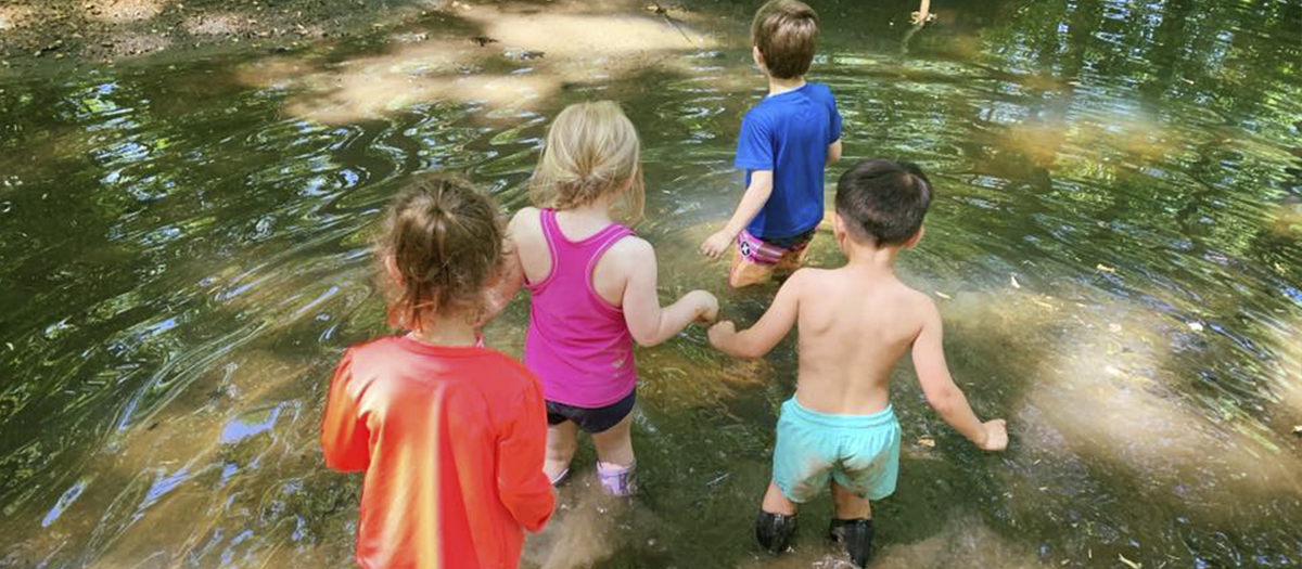 Four children walking in creek at UD Lab School
