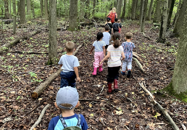 Teacher guides students through the woods outside at the UD Lab School